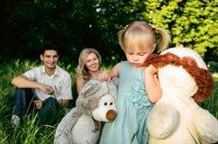 Śliczna mała dziewczynka na łące na letnim dniu z mamą i tata Zdjęcia Stock