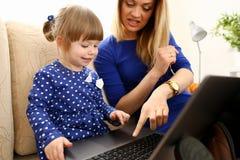 Śliczna mała dziewczynka na leżance z mamy use laptopem Obraz Stock