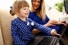 Śliczna mała dziewczynka na leżance z mamy use laptopem Obrazy Stock