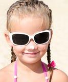 Śliczna mała dziewczynka namaszcza jej nos ochronną śmietankę fotografia royalty free