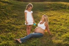 Śliczna mała dziewczynka nawadnia jej matki brzucha Zdjęcie Royalty Free
