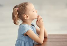 Śliczna mała dziewczynka ono modli się w domu zdjęcia royalty free