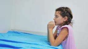 Śliczna mała dziewczynka ono modli się w domu mała dziewczynka ono modli się w wieczór przed pora snu łóżkiem mała dziewczynka i  zdjęcie wideo