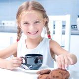 Śliczna mała dziewczynka pije herbaty z ciastkami Obrazy Royalty Free