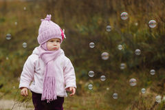 Śliczna mała dziewczynka przy parkowym łapaniem gulgocze w jesieni Obrazy Royalty Free