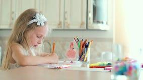 Śliczna mała dziewczynka siedzi przy stołem i rysuje z ołówkami zdjęcie wideo