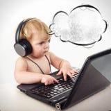 Śliczna mała dziewczynka siedzi przy stołem z jej czarnym laptopem, isol Zdjęcie Royalty Free
