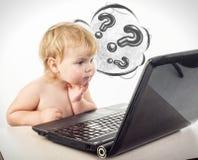 Śliczna mała dziewczynka siedzi przy stołem z jej czarnym laptopem, isol Fotografia Royalty Free