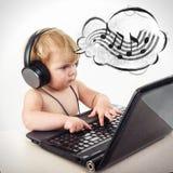 Śliczna mała dziewczynka siedzi przy stołem z jej czarnym laptopem, isol Zdjęcia Stock