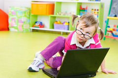 Śliczna mała dziewczynka w szkłach z laptopem na podłoga Zdjęcia Stock