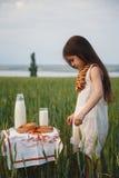 Śliczna mała dziewczynka stoi blisko małego stołu z mlekiem i chlebem na nim w zieleni polu w biel sukni Lato Fotografia Royalty Free