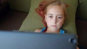 Śliczna mała dziewczynka trzyma cyfrowego pastylki lying on the beach w łóżku Nastoletnia dziewczyna bawić się na pastylka komput zdjęcie wideo