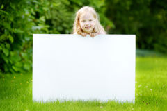 Śliczna mała dziewczynka trzyma dużego pustego whiteboard na pogodnym letnim dniu outdoors Obraz Stock
