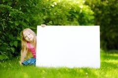 Śliczna mała dziewczynka trzyma dużego pustego whiteboard na pogodnym letnim dniu outdoors Zdjęcia Royalty Free