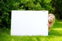 Śliczna mała dziewczynka trzyma dużego pustego whiteboard na pogodnym letnim dniu outdoors Fotografia Stock