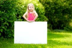 Śliczna mała dziewczynka trzyma dużego pustego whiteboard na pogodnym letnim dniu outdoors Zdjęcia Stock