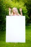 Śliczna mała dziewczynka trzyma dużego pustego whiteboard na pogodnym letnim dniu outdoors Obrazy Royalty Free