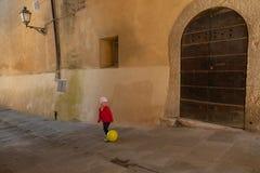 Śliczna mała dziewczynka ubierał w czerwieni bawić się z koloru żółtego balonem na t Obrazy Royalty Free