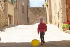Śliczna mała dziewczynka ubierał w czerwieni bawić się z koloru żółtego balonem na t Fotografia Royalty Free