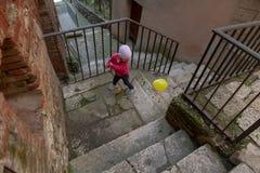 Śliczna mała dziewczynka ubierał w czerwieni bawić się z koloru żółtego balonem na t Obraz Stock