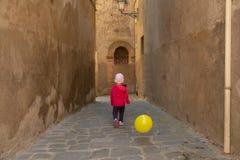 Śliczna mała dziewczynka ubierał w czerwieni bawić się z koloru żółtego balonem na t Zdjęcie Royalty Free