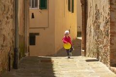 Śliczna mała dziewczynka ubierał w czerwieni bawić się z koloru żółtego balonem na t Obrazy Stock