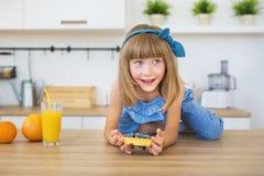Śliczna mała dziewczynka w błękit sukni siedzi na stole i chce jeść ciastko Fotografia Stock