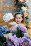 Śliczna mała dziewczynka w białej koronkowej sukni daje białego kwiatu Fotografia Stock