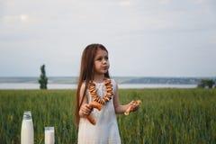Śliczna mała dziewczynka w biel sukni łasowania bagel z mlekiem w zieleni polu, lato Obrazy Stock