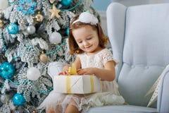 Śliczna mała dziewczynka w bklom sukni obsiadaniu w krześle i otwiera pudełko z teraźniejszością dla tło choinki błękita zdjęcie stock