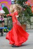 Śliczna mała dziewczynka w czerwonym kostiumu tanczy na ulicie Dziewczyna w taniec klasie Dziewczynka uczy się tana Pokazuje tana obraz royalty free