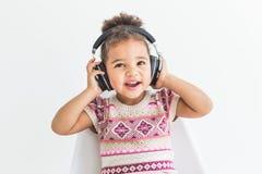 Śliczna mała dziewczynka w kolorowym smokingowym słuchaniu muzyka z hełmofonami na białym tle zdjęcie stock