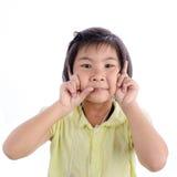 Śliczna mała dziewczynka w kolorze żółtym robi śmiesznej twarzy obraz stock