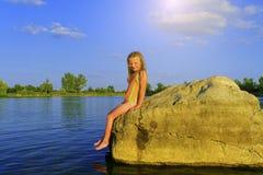 Śliczna mała dziewczynka w kostiumu kąpielowego obsiadaniu na wielkiej skale jeziorem przy zmierzchem Lato i szczęśliwy dziecińst obraz stock