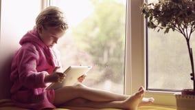 Śliczna mała dziewczynka w różowym bathrobe używać pastylka komputer osobistego podczas gdy Siedzący na nadokiennym parapecie zbiory