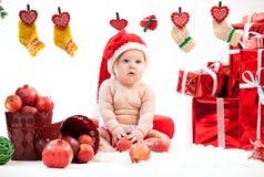 Śliczna mała dziewczynka w Santa kapeluszowym obsiadaniu na podłoga Obraz Stock