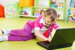 Śliczna mała dziewczynka w szkłach z laptopem na podłoga Zdjęcie Royalty Free