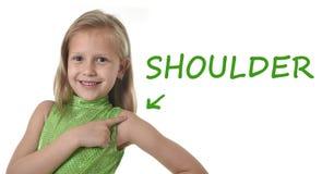 Śliczna mała dziewczynka wskazuje jej ramię w częściach ciała uczy się angielszczyzn słowa przy szkołą Zdjęcia Royalty Free