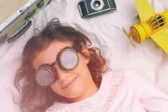 Śliczna mała dziewczynka z śmiesznymi pilotowymi szkłami bawić się z samolotem Obraz Royalty Free
