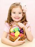 Śliczna mała dziewczynka z koszykowy pełnym kolorowi Easter jajka Obraz Stock