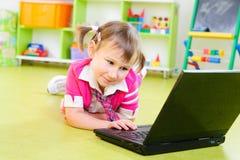 Śliczna mała dziewczynka z laptopem na podłoga Zdjęcie Royalty Free