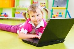 Śliczna mała dziewczynka z laptopem na podłoga Zdjęcia Stock