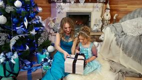 Śliczna mała dziewczynka z mum patrzeje Bożenarodzeniowego prezent i odpakowywa, pięknie pakującego w opakunkowym papierowym pude zbiory