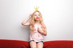 Śliczna mała dziewczynka z papierową koroną i czerwonymi wargami siedzi na czerwonym krześle w domu Zdjęcia Stock