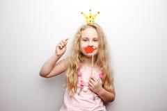 Śliczna mała dziewczynka z papierową koroną i czerwonymi wargami siedzi na czerwonym krześle w domu Zdjęcie Stock