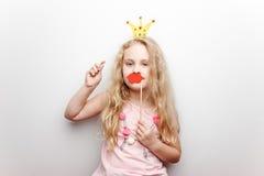 Śliczna mała dziewczynka z papierową koroną i czerwonymi wargami siedzi na czerwonym krześle w domu Zdjęcie Royalty Free