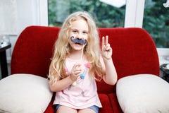 Śliczna mała dziewczynka z papierowymi wąsami podczas gdy siedzący na czerwonym krześle w domu Zdjęcie Royalty Free