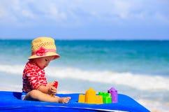 Śliczna mała dziewczynka z piaskiem bawi się na plaży Zdjęcia Stock