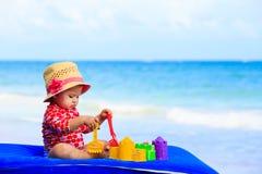 Śliczna mała dziewczynka z piaskiem bawi się na plaży Obrazy Stock