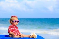 Śliczna mała dziewczynka z seashells na plaży Fotografia Royalty Free
